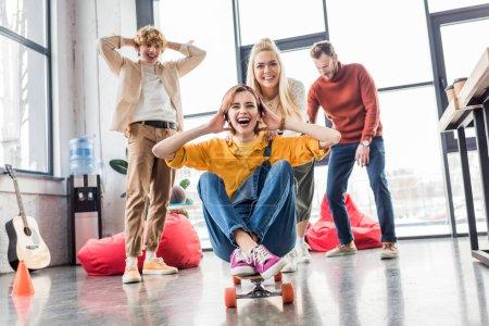 Photo pour Collègues de vêtements de travail heureux s'amuser et de l'équitation de skateboard au bureau loft - image libre de droit