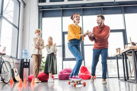 Photo for Smiling casual business colleagues having fun and riding skateboard in loft office - Royalty Free Image