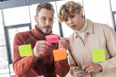 Photo for Handsome casual businessmen putting colorful sticky notes on glass window in office - Royalty Free Image