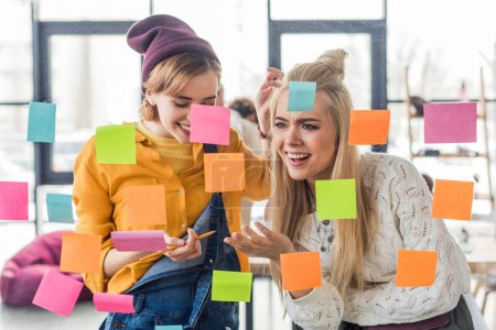 Photo for Beautiful casual businesswomen laughing near colorful sticky notes on glass window in office - Royalty Free Image