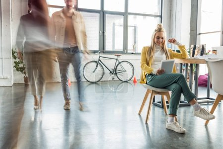 Photo for Smiling casual businesswoman sitting and using digital tablet in loft office with colleagues in motion blur on background - Royalty Free Image