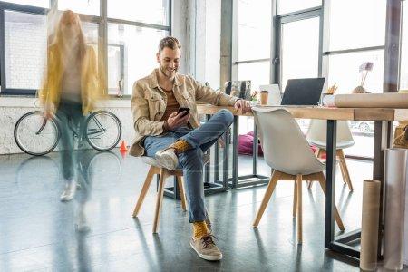 Photo pour Architecte masculin assis et à l'aide de smartphone avec le collègue en mouvement flou sur l'arrière-plan de bureau loft - image libre de droit
