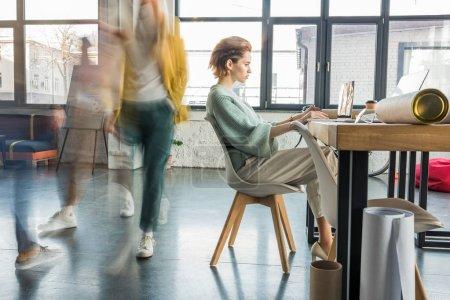 Foto de Mujer arquitecto sentado y utilizando la computadora portátil en el escritorio en la oficina de loft con colegas en el movimiento desenfoque en el fondo - Imagen libre de derechos