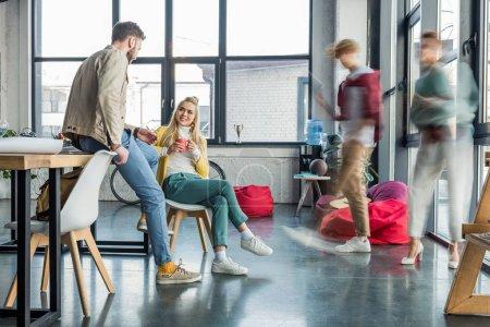 Photo pour Mâles et femelles des entrepreneurs occasionnels assis et avoir la discussion dans le bureau loft avec des collègues en mouvement flou sur le fond - image libre de droit