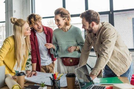 Foto de Feliz grupo de arquitectos mujeres y hombres trabajando en el plano en el escritorio en la oficina de loft - Imagen libre de derechos