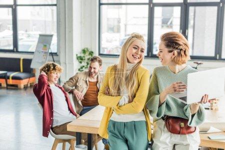 Photo pour Belle souriant décontracté femmes chefs d'entreprise à l'aide d'ordinateur portable et travaillant sur le projet de démarrage dans le bureau loft avec des collègues masculins sur fond - image libre de droit