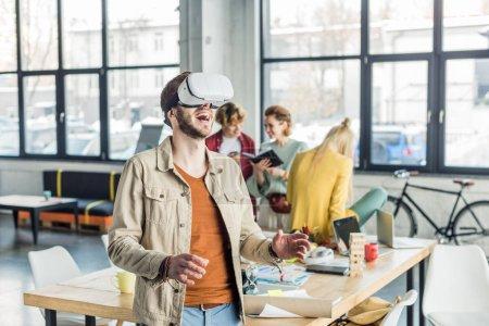 Photo pour Excité designer masculin geste avec les mains tout en ayant une expérience de réalité virtuelle dans le bureau loft avec des collègues sur fond - image libre de droit