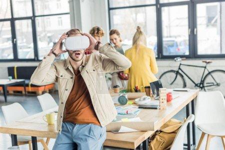 Photo pour Surpris designer masculin geste avec les mains tout en ayant une expérience de réalité virtuelle dans le bureau loft avec des collègues sur fond - image libre de droit