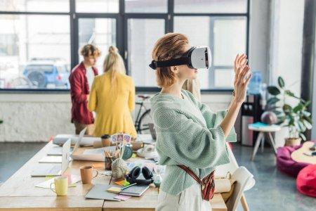 Photo pour Gesticulant concepteur femelle avec les mains tout en ayant une expérience en bureau loft avec ses collègues sur fond de réalité virtuelle - image libre de droit