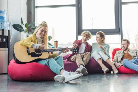 Photo for Happy group of friends sitting on bean bag chairs and playing guitar - Royalty Free Image