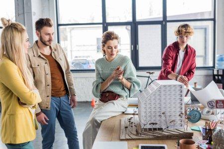 Foto de Concentrado grupo de arquitectos mujeres y hombres trabajando juntos en la casa modelo en la oficina de loft - Imagen libre de derechos