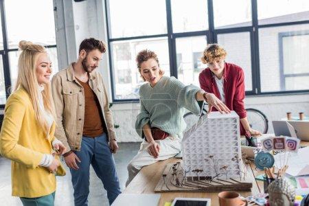 Photo pour Groupe de mâles et femelles architectes travaillent ensemble sur le modèle de maison dans le bureau loft - image libre de droit