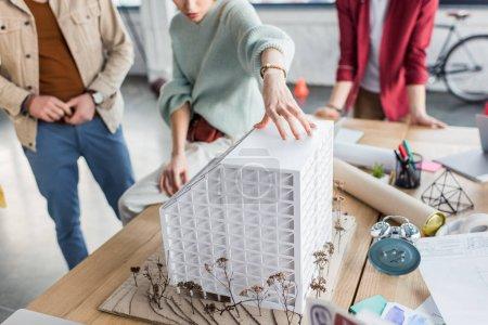 Photo pour Recadrée vue du groupe des architectes féminins et masculins travaillant ensemble sur le modèle de maison dans le bureau loft - image libre de droit