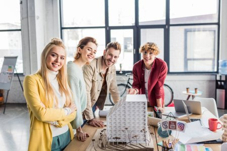 Photo for Smiling group of female and male architects working together on house model in loft office - Royalty Free Image