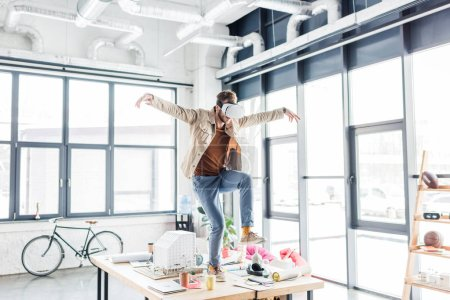 Photo for Male designer gesturing with hands while having virtual reality experience in loft office with copy space - Royalty Free Image