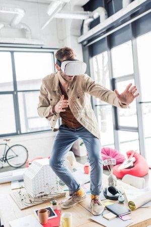 Photo pour Surpris architecte mâle gesticulant avec les mains tout en ayant une expérience en bureau loft de réalité virtuelle - image libre de droit