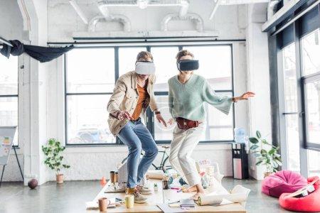Photo pour Mâles et femelles architectes vr vous le portez, gestuelle des mains et avoir de réalité virtuelle expérience bureau loft - image libre de droit