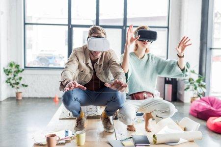 Photo pour Architectes excités femmes et hommes gesticulant avec les mains tout en ayant une expérience de réalité virtuelle dans le bureau loft - image libre de droit