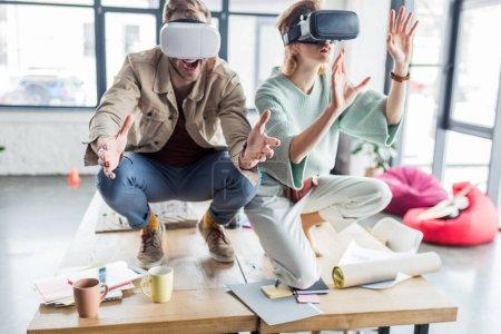 Photo pour Mise au point sélective des excités architectes féminins et masculins, gesticulant avec les mains tout en ayant une expérience en bureau loft de réalité virtuelle - image libre de droit
