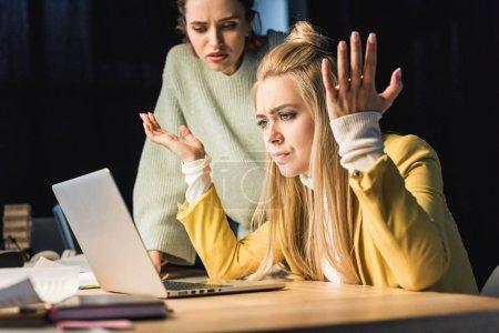 Photo pour Belle femelle confuse il spécialistes utilisant l'ordinateur portable au bureau - image libre de droit