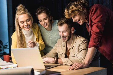 Photo for Smiling group of it specialists using laptop in office - Royalty Free Image