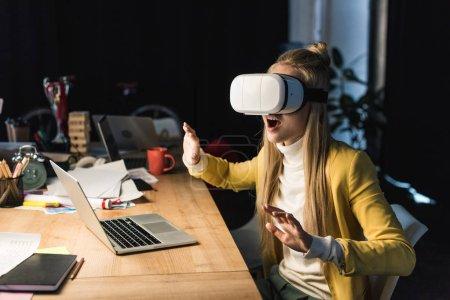 Photo pour Excité de femme d'affaires occasionnel, gesticulant avec les mains tout en ayant une expérience en bureau d'ordinateur de bureau de réalité virtuelle - image libre de droit
