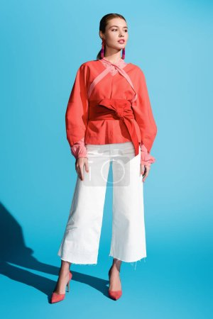 Photo for Fashionable woman posing in living coral clothing on blue - Royalty Free Image