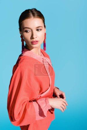 Photo pour Femme à la mode qui pose en tendance vivant vêtements corail isolé sur bleu - image libre de droit