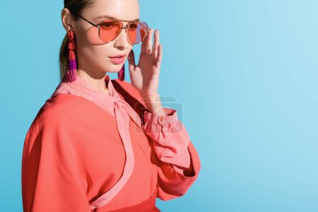Photo for Beautiful stylish girl in trendy living coral clothing and sunglasses posing isolated on blue - Royalty Free Image