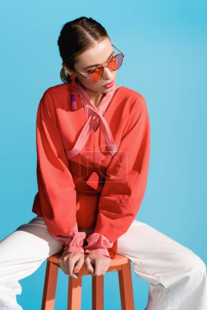 Photo for Stylish woman in trendy living coral clothing and sunglasses posing on stool isolated on blue - Royalty Free Image