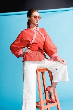 Photo pour Femme à la mode posant dans des vêtements de corail vivant et des lunettes de soleil sur bleu - image libre de droit