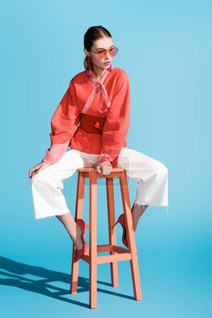 fashionable woman in living coral clothing and sunglasses posing on stool on blue
