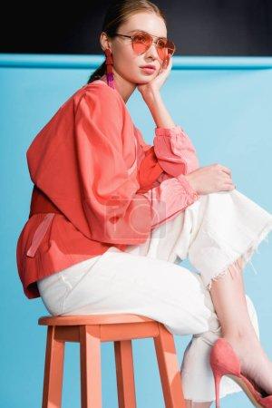 Photo pour Fille à la mode dans des vêtements de corail de vie à la mode et des lunettes de soleil posant sur tabouret sur turquoise - image libre de droit