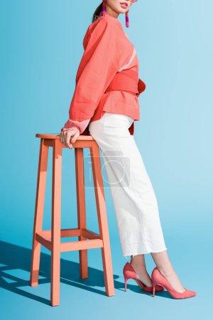 Photo pour Vue recadrée de la femme élégante dans des vêtements de corail vivant à la mode posant sur des tabourets sur bleu - image libre de droit