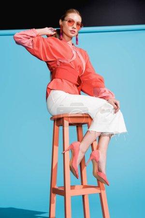 Photo pour Élégante femme à la mode dans des vêtements de corail vivant à la mode et des lunettes de soleil assis sur tabouret sur bleu - image libre de droit