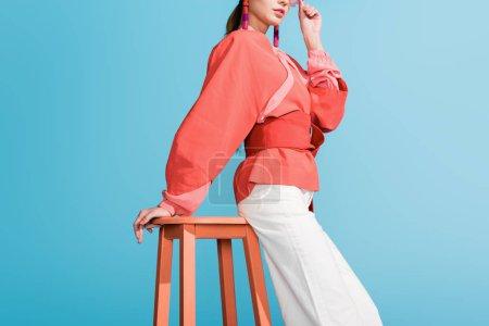 Photo pour Vue recadrée de la femme dans des vêtements de corail vivant à la mode posant sur des selles isolées sur bleu - image libre de droit