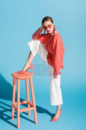 Photo pour Modèle élégant en vêtements corail vivant et lunettes de soleil posant sur tabouret sur bleu - image libre de droit