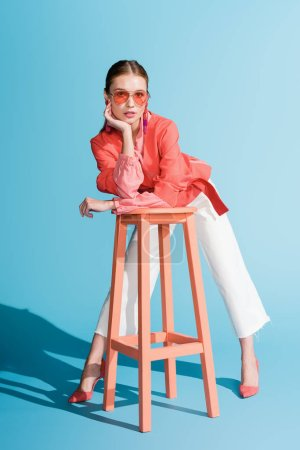 Photo for Fashionable model in living coral clothing and sunglasses posing on stool on blue - Royalty Free Image