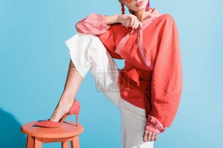 Photo pour Vue recadrée de la jeune fille dans des vêtements de corail vivant posant sur tabouret sur bleu - image libre de droit