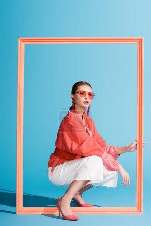Foto de Moda chica en vida coral ropa y gafas de sol con marco grande en azul - Imagen libre de derechos