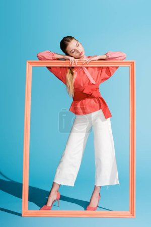 Photo pour Femme élégante à la mode dans les vêtements de corail vivant posant avec grand cadre sur bleu - image libre de droit