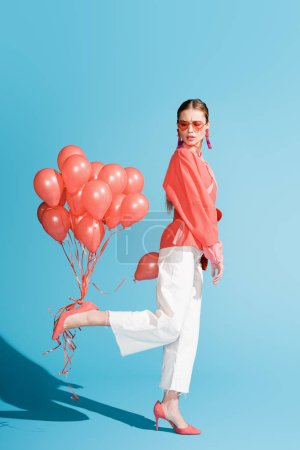 Photo for Beautiful fashionable model posing with living coral balloons on blue - Royalty Free Image