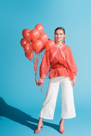 Photo for Beautiful stylish girl posing with living coral balloons on blue - Royalty Free Image