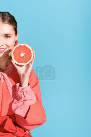 Photo for Half view of cheerful beautiful woman posing with living coral grapefruit isolated on blue - Royalty Free Image