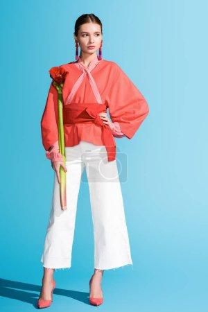 Photo pour Chic fille élégante tenant salon fleur corail sur bleu. Couleur Pantone de la notion d'année 2019 - image libre de droit