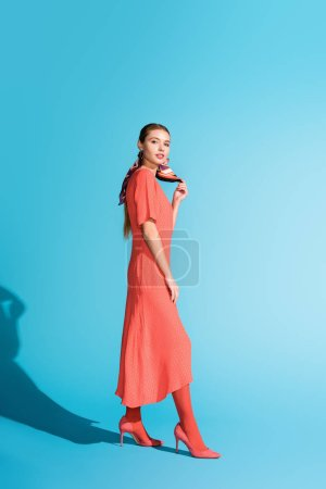 Photo for Fashionable elegant model in trendy living coral dress posing on blue - Royalty Free Image