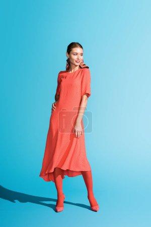 Photo pour Shooting de mode élégant modèle souriant en vie tendance robe corail posant sur bleu - image libre de droit