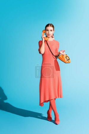 Photo for Attractive fashionable model in living coral dress posing with rotary telephone on blue - Royalty Free Image