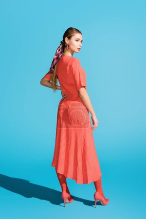 Photo for Attractive stylish girl in trendy living coral dress posing on blue - Royalty Free Image
