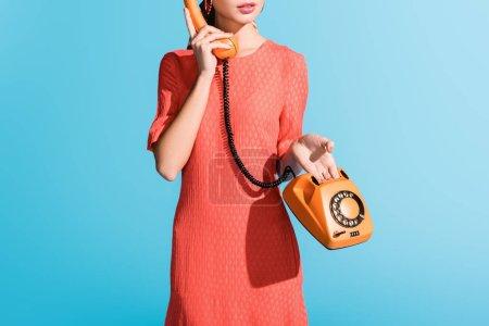 Foto de Vista recortada de la mujer en la vida coral vestido posando con teléfono rotatorio aislado en azul - Imagen libre de derechos